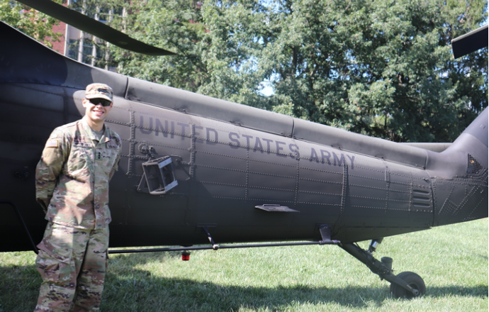 Cadet in front of a Blackhawk helicopter